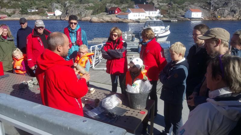 Arkeolog viser frem funn fra sjøbunnen til en gruppe besøkende på brygga.