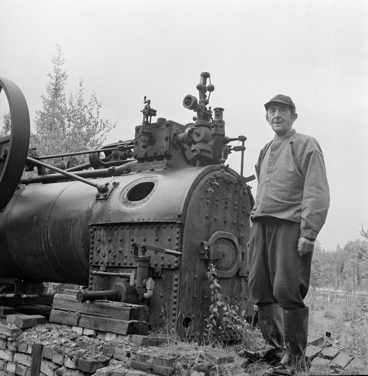 Dampmaskin, levert av O. Jakobsons maskinverksted i Kristiania, brukt på et sagbruk i Eidskog.  Her stod den ved en myrkant, delvis på et underlag av krysslagte bjelker, dels på en teglsteinsmurt oven som var bygd etter et prinsipp som var utviklet av Lauritz Sæthern (1866-1935) i Eidskog.  På dette bildet ser vi grunneier Harry Pramhus (1891-1973) posere framfor lokomobilen.  Ole Jakobson var husmannssønn fra Hedmarken.  Han fikk bare folkeskoleutdanning, men som ung voksen fikk han stillingen som pedell ved Katedralskolen i hovedstaden.  Der skal han ha fått muligheter for å lære.  Det var særlig tekniske fag som interesserte Jakobson, og i 1845 startet han sitt eget verksted.  Der produserte han blant annet maskiner for landbruket, som han kjente godt fra sitt eget oppvekstmiljø.  Etter Jakobsons død ble virksomheten overtatt av sønnen, som hadde fått reise til USA for å ta den formelle utdanninga faren manglet.  Han flyttet verkstedet fra de opprinnelige lokalene i Torggata 11 til Nedre Foss, i nyere tid bedre kjent som Vulkan.  I 1894 fikk bedriften nye eiere, som flyttet virksomheten til Schultzehaugen.  Produktspekteret ble gradvis vridd fra landbruksmaskiner til vaskemaskiner (varemerket «JAKO») og klesruller.
