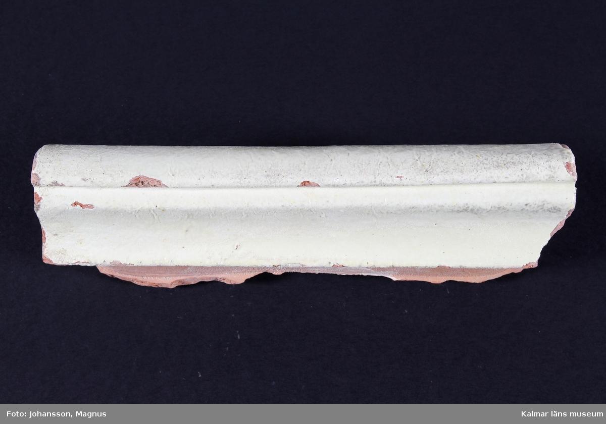 """KLM 38941. Kakel. Från flera kakelugnar. Blyglasyr på vit engobe och röd lergodsskärv. Reliefkakel med drejad rump eller helt formpressade kakel eller i kombination.  Förteckning över samtliga kakel, med mått inom parentes, gjord i samband med inventering 1997:   :1. 17 st. friskakel         (18x24x5,5 cm) med drejad rump     3 st.  -""""-                   (18x13x6 cm)  -""""-       1 st.  -""""-                   (18x7x1 cm)  -""""-       9 st.  hörnfris           (18x16,5x11 cm)  -""""-   :2. 13 st. friskakel         (18x25,5x5 cm) med drejad rump, varav 1 med grön engobedekoration :3. 8 st. friskakel           (18x23,5x5 cm ) med drejad rump     1 st.  -""""-                   (18x18x5,5 cm) -""""-       2 st.  hörnfris           (18,5x16x7,5 cm) -""""-   :4. 4 st. friskakel           (19x24,5x5 cm) med drejad rump     1 st.  -""""-                   (19x18x5 cm) -""""-       2 st. hörnfris             (19x17x10,5 cm) -""""-   :5. 5 st. krönkakel         (14x22,5x4,5 cm) helt formpressade     1 st. hörnkrön          (14x23x10 cm) -""""-   :6. 9 st. krönkakel         (12x23,5x13 cm) helt formpressade     4 st. hörnkrön          (12x21x13 cm) -""""-   :7. 6 st. friskakel           (13x22x6,5 cm)med drejad rump     1 st. hörnfris            (13x16x11 cm) -""""-   :8. 1 st. fotsims            (12,5x25x5,5 cm)     2 st. hörnfot            (9,5x23x11 cm)     2 st. mittsims           (6x24x4,5 cm)     1 st. hörn                (6,5x19x11 cm)     1 st. hörnfot            (7,5x16x12,5 cm)     3 st. fotsims            (6x22,5x5,5 cm)     1 st. hörnfot            (6x19,5x13 cm) :9. 2 st. mittsims          (7,5x21x9 cm) :10. 13 st. fotsims        (13x24x10 cm) med drejad rump        4 st.  -""""-               (13x12x10 cm) -""""-           2 st. hörn             (12x28x20 cm) -""""-           3 st.  -""""-               (11,5x27x17 cm) -""""-           1 st.  -""""-               (12,5x27x19 cm) -""""-    :11. 25-tal fragment"""