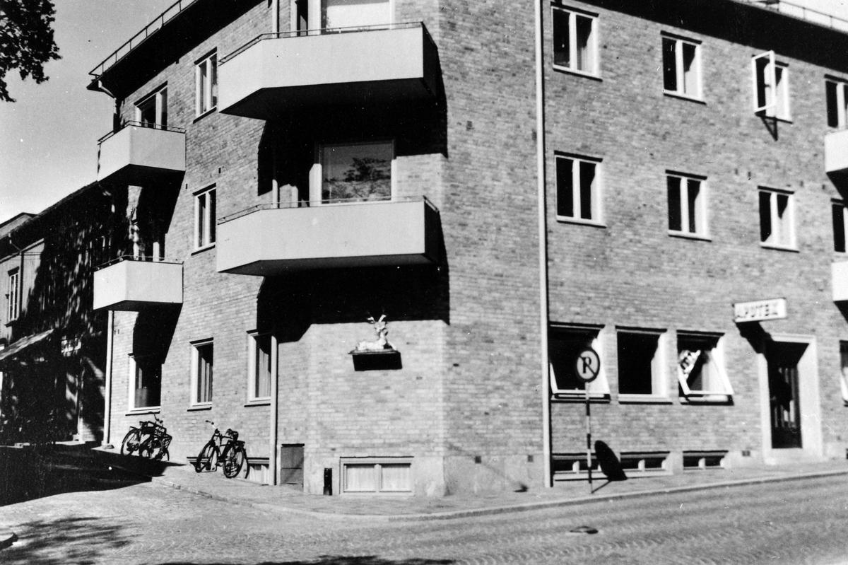 """Gatuvy av kvarteret Storken och byggnaden där apoteket Hjorten låg mellan 1946-1970. På väggen hänger en skylt med """"Apotek"""" och på byggnadens hörn är apotekets gyllene hjort uppsatt.   Apoteket mellan 1862-1946 i kv Kronan 4,  1946-1970 i kv Storken 9,  1970-1985 i kv Färgaren 11,  1985- kv Storken 11"""