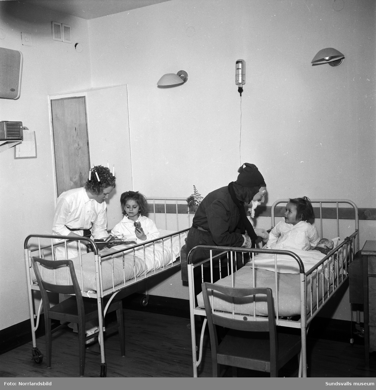 Luciafirande på barnsjukhuset. En flicka verkar inte helt bekväm med att skaka hand med tomten.