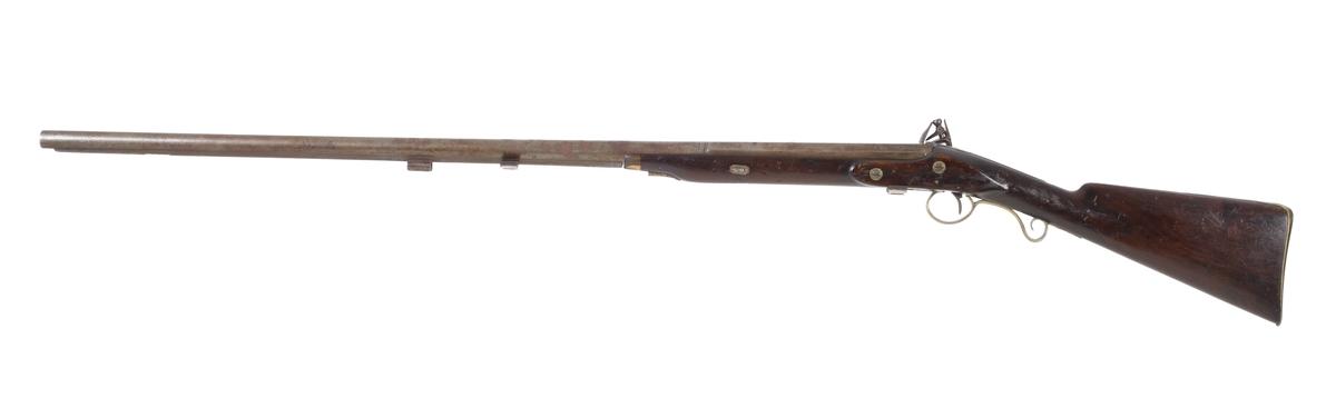 Jaktgevär försett med flintlås. Geväret har en kort framstock med näsbeslag i horn. Laddstocken sitter i tre rörkor varav spetsrörkan är i mässing. Kolven är slät och odekorerad, förutom kolvhalsen som har en ytterst tunn nätskärning. Bakplåten går upp över kolvryggen och avslutas med en spets. Bakplåt och varbygel i mässing, och låsbleck har graverad bladdekor. Pipan är rund och övergår i en åttakantig form baktill. Geväret har ett filat gropsikte vid svansskruven, och korn saknas. Pipan är slätborrad och har en innerdiameter på 19 mm. Inskrivet i huvudkatalog 1974.