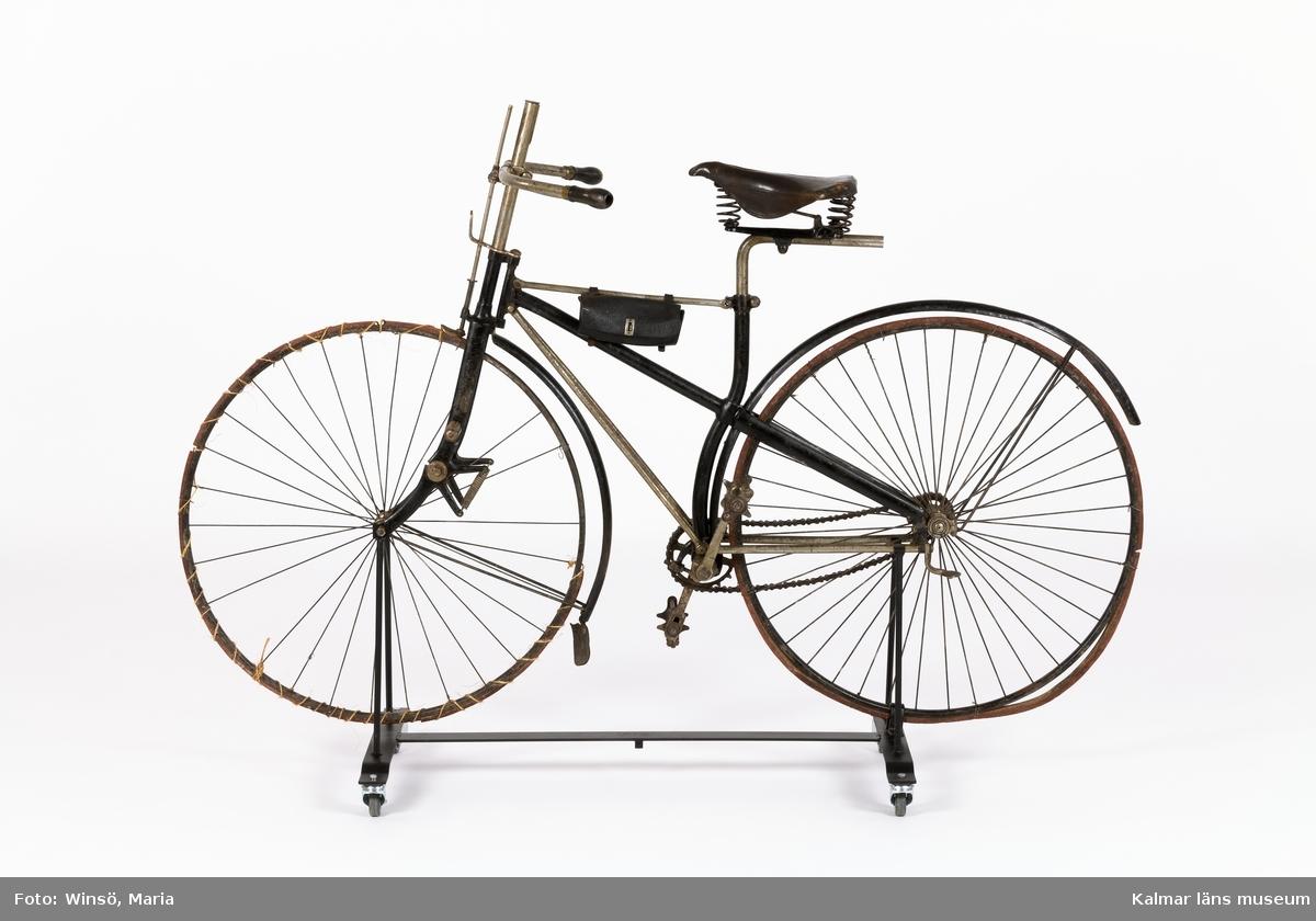 KLM 44079. Cykel. Ram av järn, hjul av stål med däck av massivt gummi och så kallat fast nav. Har förstärkt korsram. Framgaffel med fjädring. Kedja med stora länkar, dvs blockkedja. Styret är höj- och sänkbart, med broms, ett äldre patent för konstruktionen, kan ha använts på en föregångare, en damcykel eller en höghjuling. Med cykelväska. Ett stort antal stämplar, bl a olika patent nr, stämpel på metallbleck på trampor: Rudge Cycle Co Ltd, Coventry. Lanserades under benämningen säkerhetscykel. Tillverkad i England, Rudge Cycle, D Rudge & Co Ltd, Coventry. Sadel, tillverkad av Brooks (vilka tillverkar sadlar än idag).