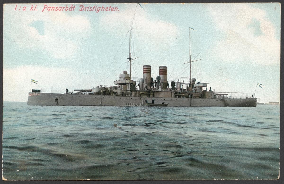Vykort som visar 1. klass pansarbåt Dristigheten till sjöss från babordssidan.