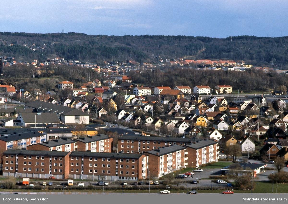 Vy över Bifrostgatan och bostadsbebyggelse på Solängen mot Åbykullen i Mölndal, april 1992. Till vänster ses även byggnader tillhörande Fässbergsgymnasiet. D 16:9.