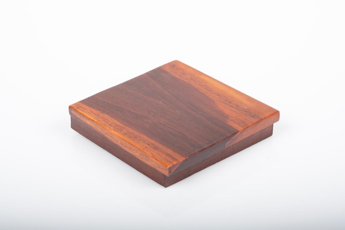 Lokk til kvadratformet, lakkert treskrin. Lokket er laget av to treslag, ett lysere inni og ett mørkere utenpå. Delene er limt sammen.