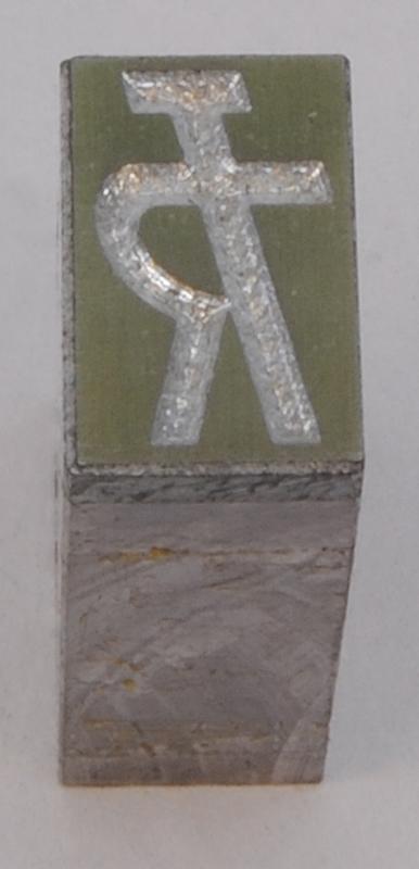 """Rektangulär kliché av silverfärgad och grön metall, monterad på en silverfärgad metallkloss. På finns Trafikrestaurangers logotyp med bokstäverna """"TR"""" sammanlänkade i form av """"TR-pojken"""". Den kallas TR-pojken eftersom det ser ut som en person som håller armen i en serveringsgest. Logotypen är präglad."""