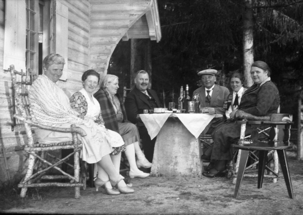 Gruppe mennesker sitter ved Vester-Holm.