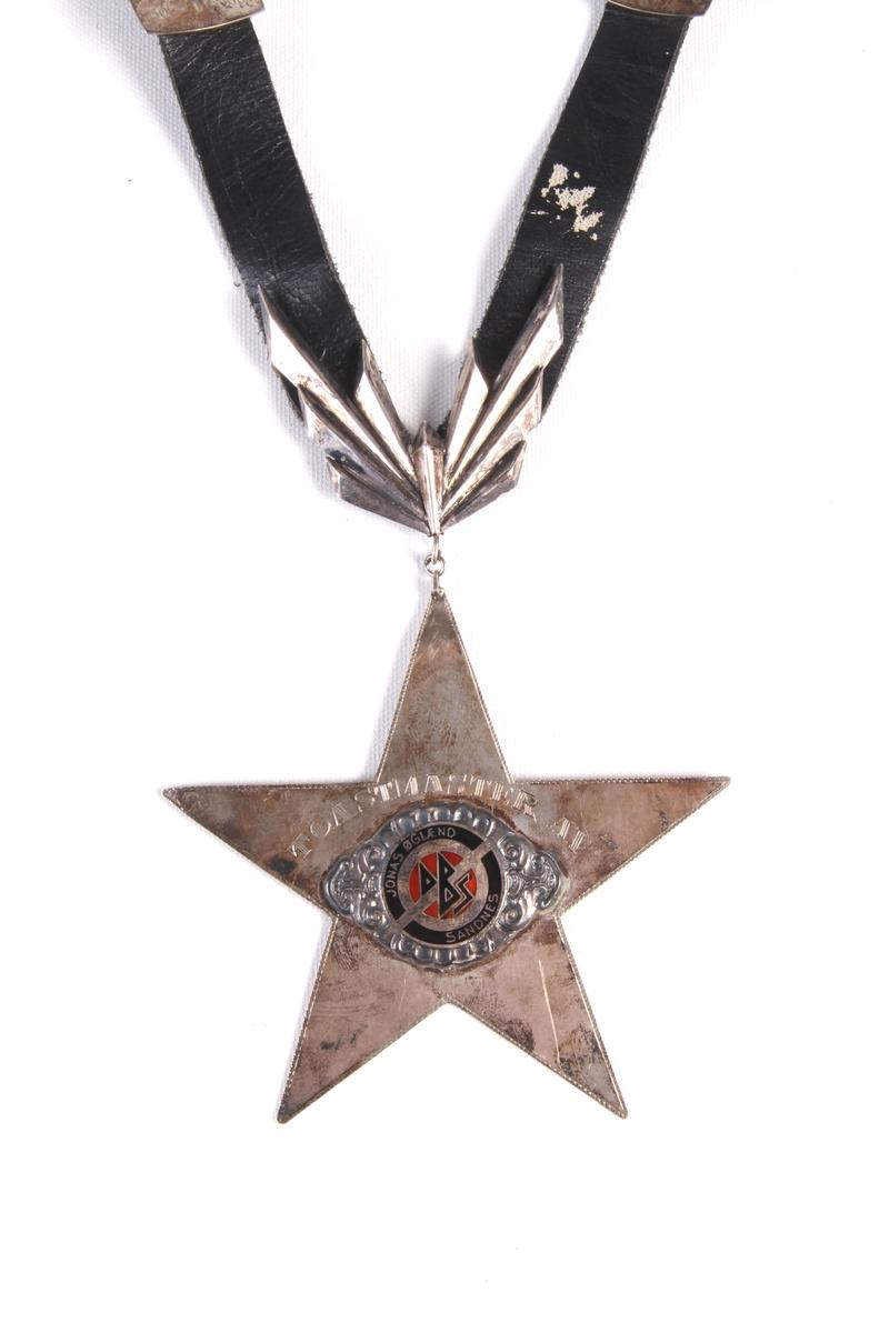 Halskjede av lær med stjerneformet sølvplate med innskrift. Platene langs sidene er signert av brukerne.