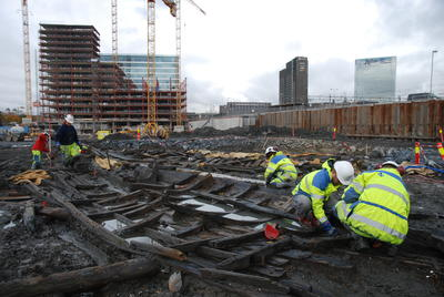 Tre arkeologer i gult arbeidstøy og med hvite hjelmer sitter på huk og graver i restene av en trebåt som ligger i gjørme. Båten er delvis fylt med vann. En arkeolog i bakgrunnen spar i leire med spade. I bakgrunnen ses Postgirobygget, SAS-hotellet og kjøreledninger til tog over skinnene på Oslo S. Et bygg under oppføring, omgitt av kraner og anleggsmaskiner, står på andre siden av samme tomt som arkeologene arbeider på.