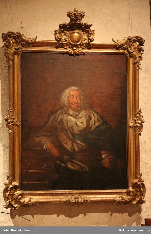 Porträtt av Fredik I, knäbild, sittande enface i vit peruk. Livrock av brokadsiden, kunglig mantel med guldkronor, broderade mot blå botten på ena sidan och hermelin på andra. Till vänster ett bord med krona, spira, äpple och nyckel. Rött draperi som bakgrund.