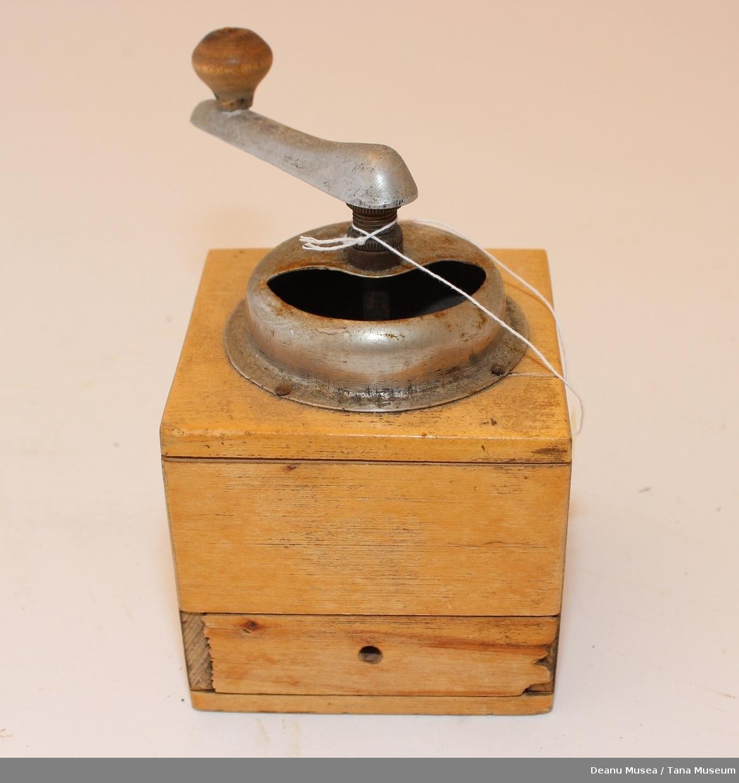 Kaffekvern i tre. Skuffen for å ta ut kvernet kaffen mangler håndtaket. Innmaten og sveiven er av metal.