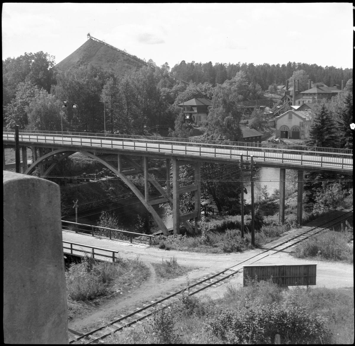 I förgrunden syns landsvägsbron, som byggdes 1934. I bakgrunden slagghögen och delar av järnbruket.