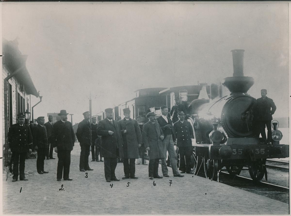 Sandträsk station på linjen Boden - Gällivare. Station anlagd 1896. En- och enhalvvånings stationshus i trä, moderniserat 1944. Mekanisk växelförregling.  Bland personalen syns: 1.Stinsen i Sandträsk 2.Grosshandlare B. Sundtröm, Luleå 3.Pastiljon Brännström 4.Konsul Broms 5.Kamrer Liasmöe, Luleå 6.Postmästare Swensen, Boden 7.Ingenjör Broms. Övriga okända. Ånglok ab 35, tillverkat 1863.