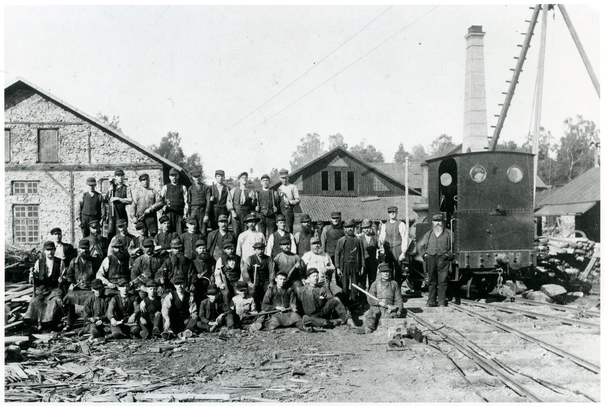 """Spikfabriken Skyllbergs bruk 1890. Personalen har ställt upp sig för fotografering. Loket är nummer 1 """"KÅRBERG""""."""