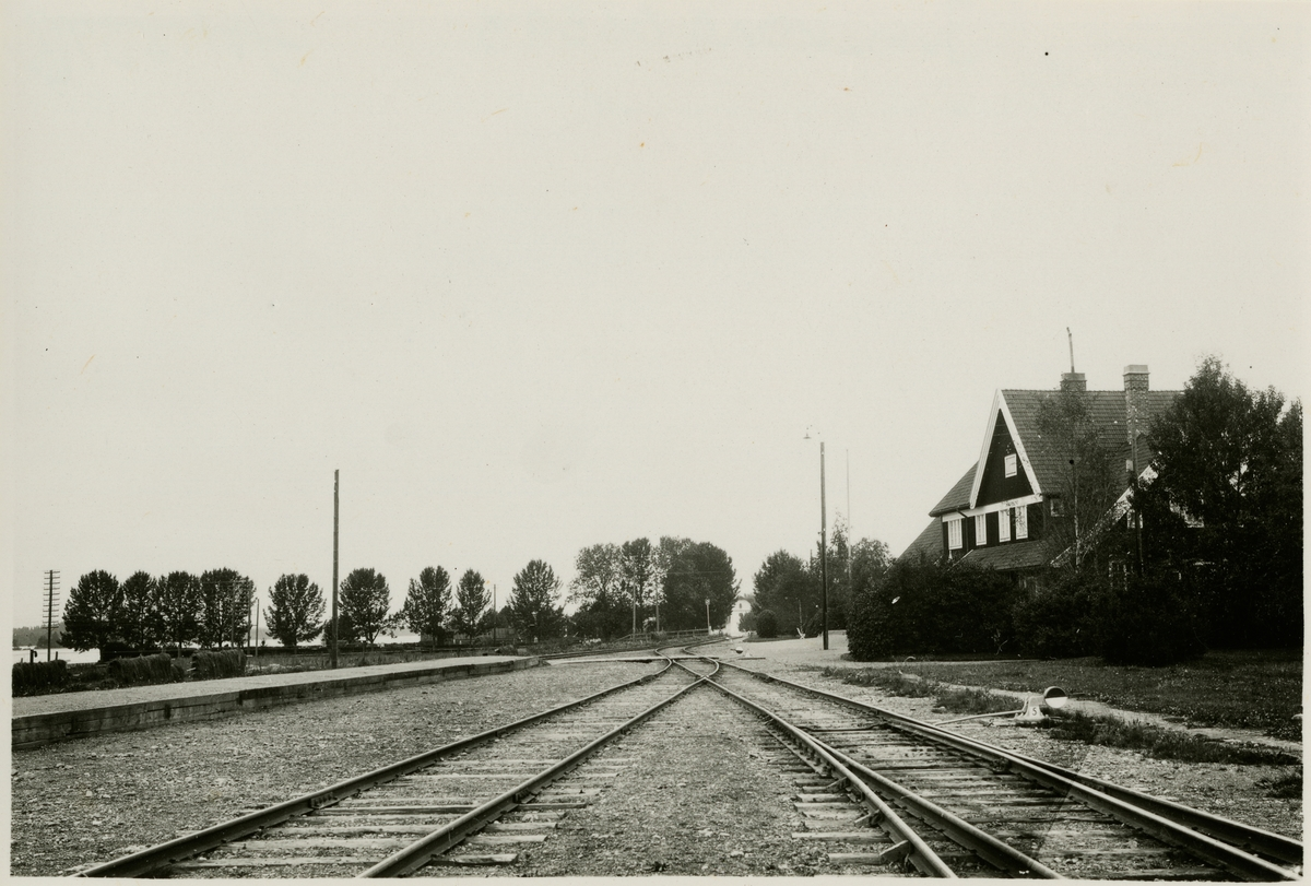 Statens Järnvägar, SJ, vattendrag till vänster och en gaslykta framför stationen.