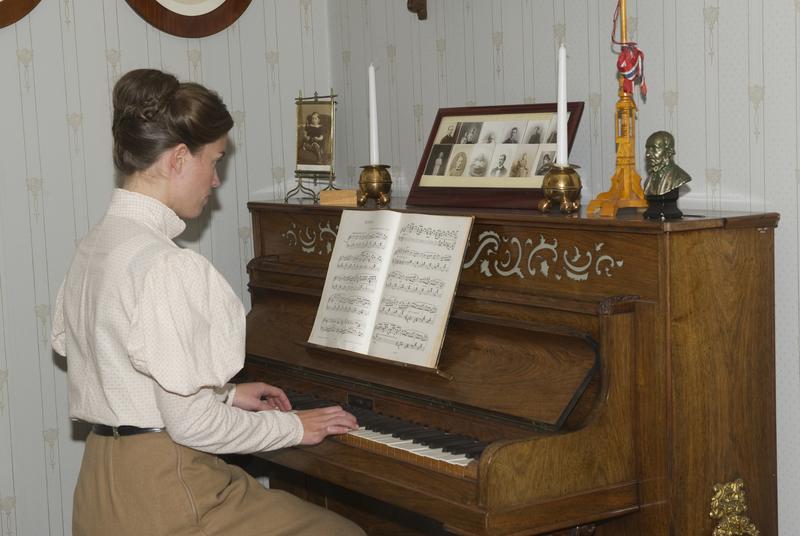 Unge fru Marie Ødegaard ved klaveret i dagligstuen.