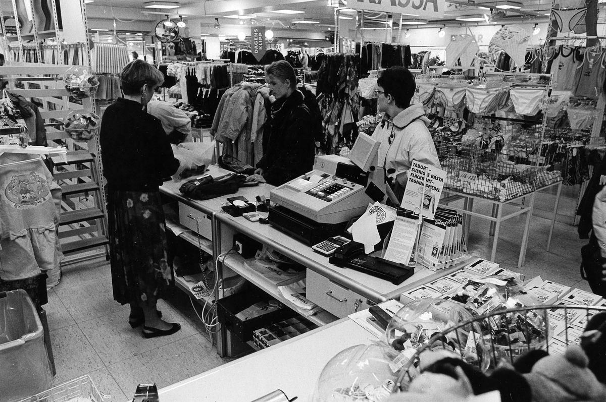En kassörska hjälper två damer vid kassan på Lindex, Kungsgatan 32, kvarter Pärlan 7. I november 1990 flyttade butiken tillsammans med Gulins (senare Adelsten) in i Epas gamla varuhus i kvarter Storken 12.
