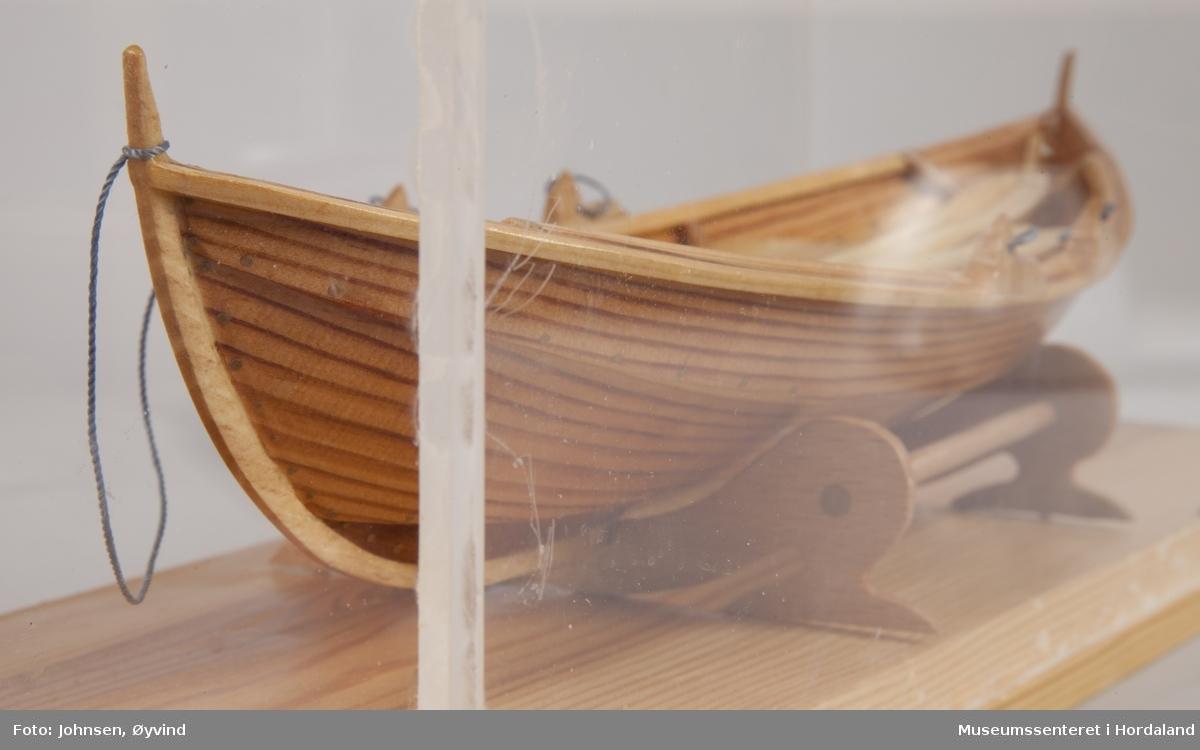 Båtmodell av Oselvar med to par årer. Satt i monter av pleksiglass og tre.