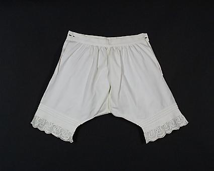 Underbyxor för barn, av vitt bomullstyg. Uddbrodyr på benen, därovanför fyra stråveck. Sprund och knapphål i sidorna upptill, tyget rynkat mot linningen.