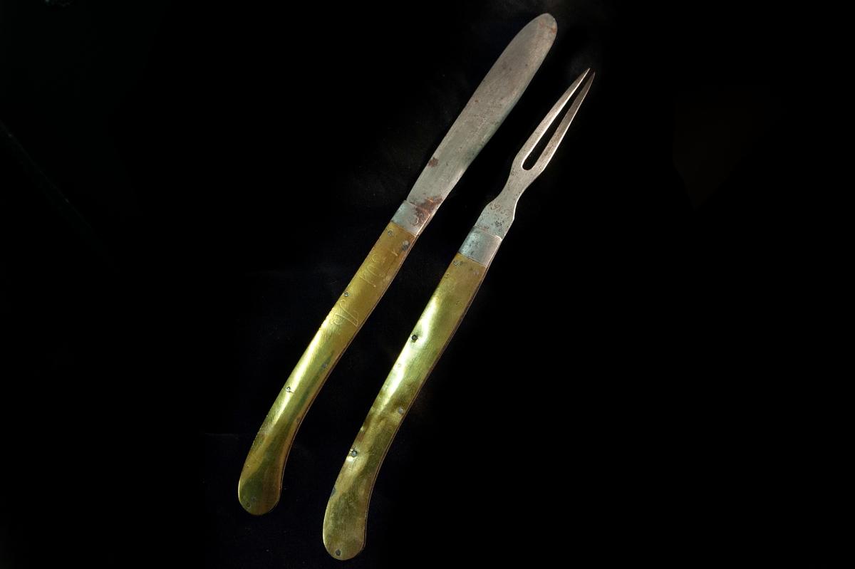 """Större kniv i fällknivsmodell i järn och mässingshandtag, del i ett set med JM.09855. Benämns som """"gästabudstyg"""" i orginalkatalog. Graverat """"1801 A"""" på ena sidan, och """"SMD"""" på andra. Stämplar saknas."""