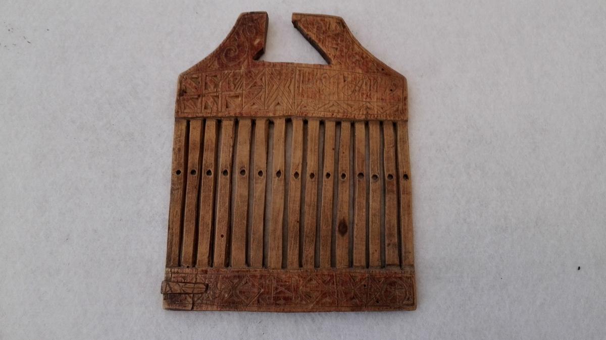 1 vevgrind.  Liten vevgrind for baandvev, 12,5 cm bred og 15,5 cm høi. Rødbeiset og forsirt med indskaarne karveskurdsornamenter og  IKS1A  1799. Gave fra Ingebrigt Rislag, Vik.