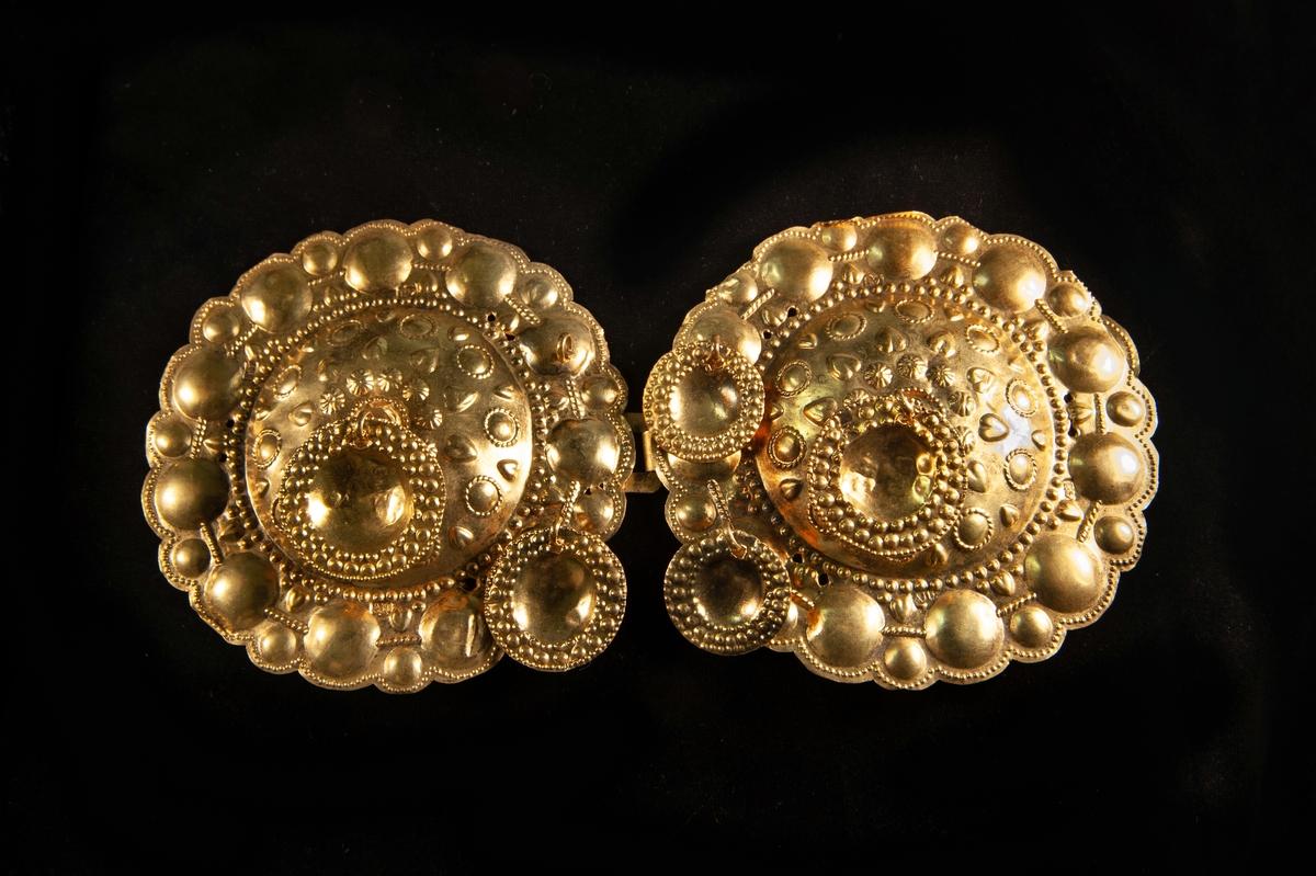 """Ett stort, runt tröjspänne av ciseleratoch förgyllt silver, med dekor av hjärtan m.m. Två runda plattor (""""skålar"""") av samma materialär fastsatta mitt på och vid ena sidan.Ursprungligen har det funnits ytterligare en sådan. Har en hyska som fästes i haken på JM.8044:2"""