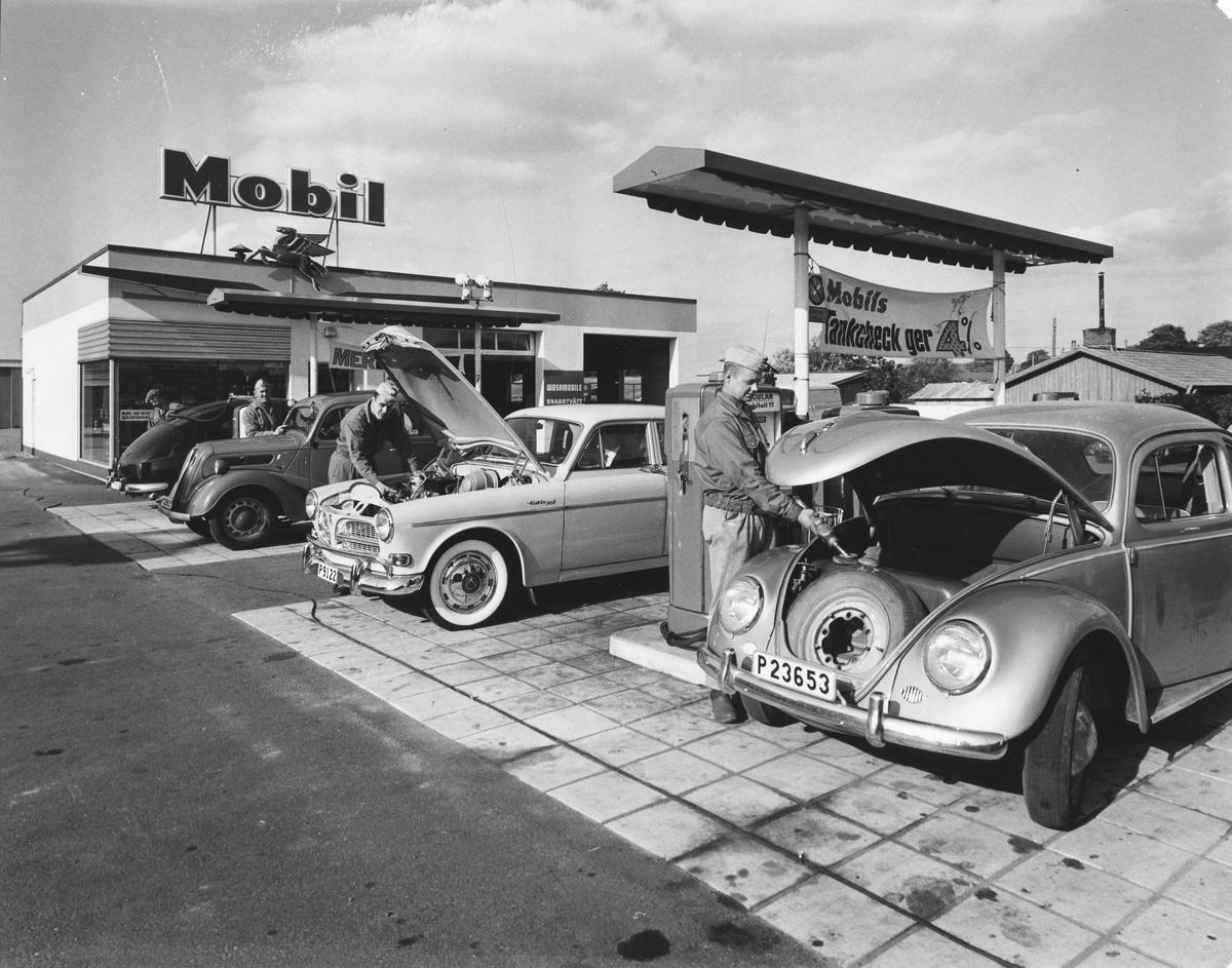 """4 män står vid varsin bil på bensinstationen """"Mobil"""", Göteborgsvägen. Fotot taget av Alingsås Tidning 1962."""