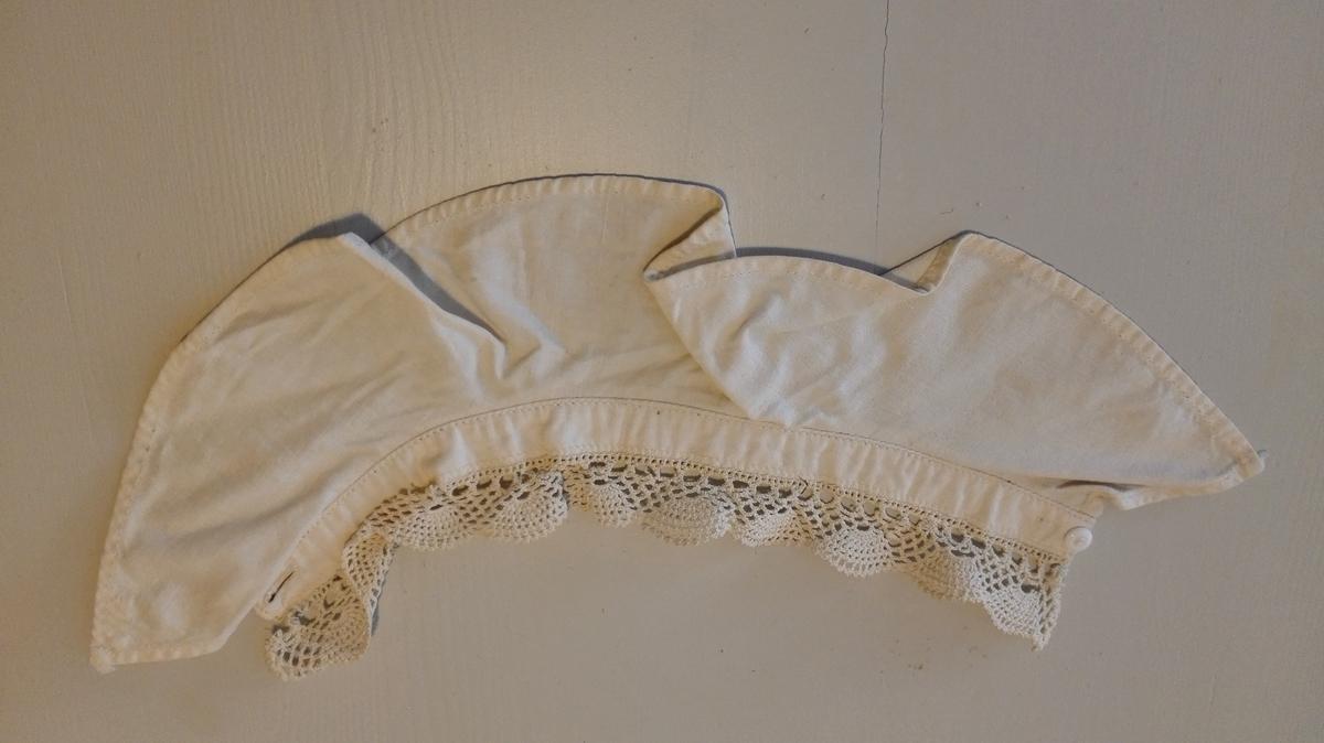 Til en smal linning - med knapp og knapphull (håndsydd) - av hvitt bomullslerret, er sydd en heimeheklet hvit blonde. Stoffet nedenfor linningen er er av samme stoff som denne. Maskinsydd.