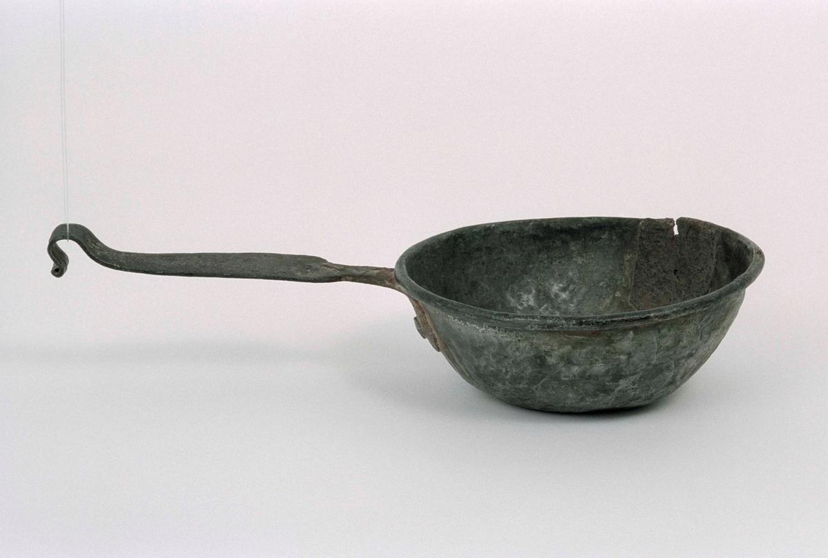 Skopa av handhamrad koppar, förtennt både ut- och invändigt. Hankfäste och skaft av järn. Lagad med metall vid ena sidan.