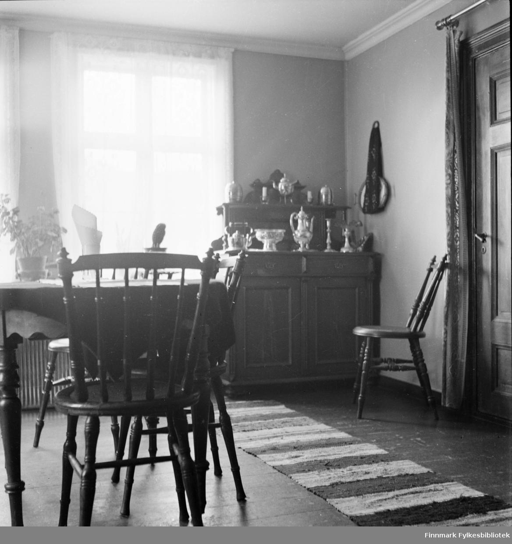 Interiør fra et hus i Kjøllefjord, fotografert i 1940. I forgrunnen sees et spisebord med dreide pinnestoler. I bakgrunnen sees et utskåret skatoll med sølvtøy servise oppstilt i flere nivåer. En fillerye ligger på gulvet.