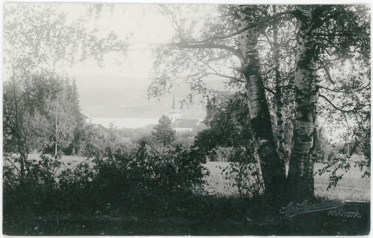 Vy tagen i Fränsta mot söder ner mot Torpsjön med Torps kyrka skymtande mitt i bild. Vykort.