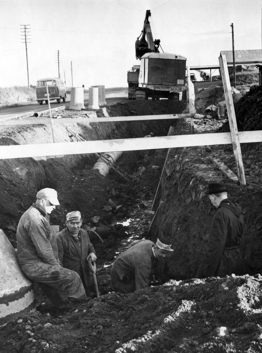 Tre män arbetar med att gräva ut en kloakledning i Noltorp.