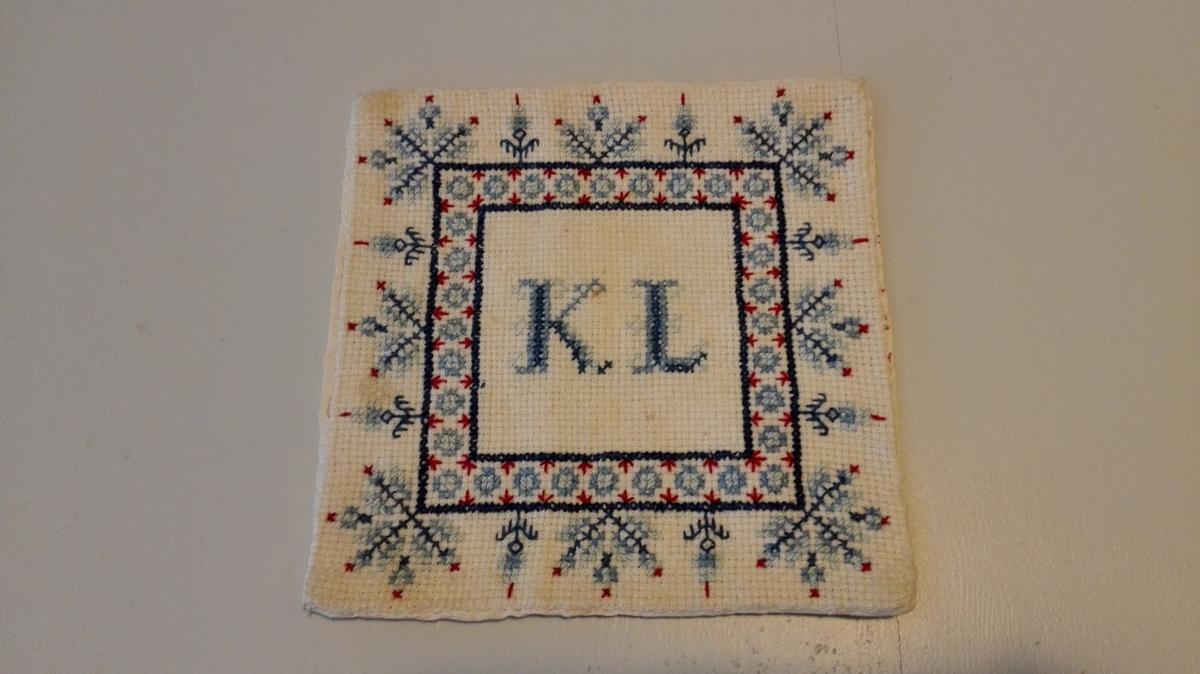 Form: Kvadratisk. Kulørt korsstingsbroderi. :Initialer på midten. Fora med cambric.