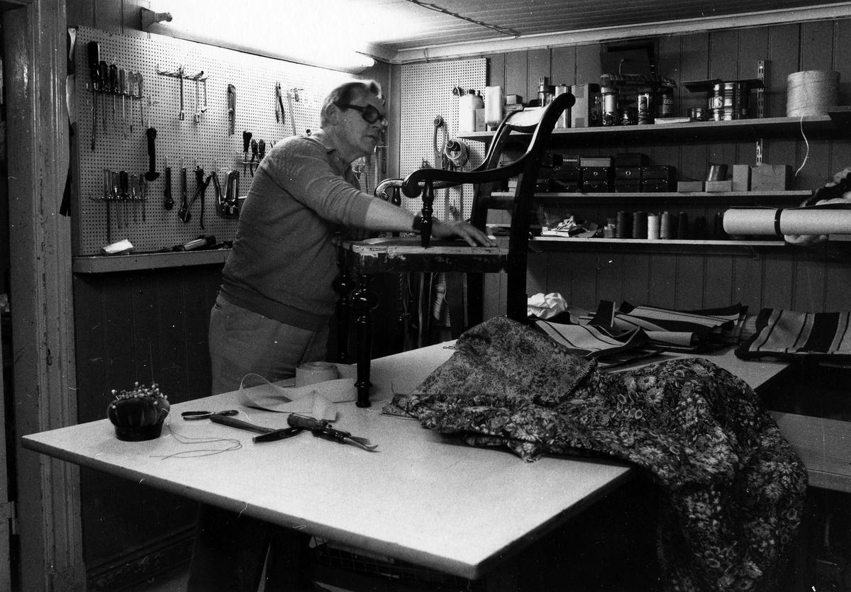Bilden visar Alf Andersson som arbetar i verkstaden på Alingsås Sadelmakeri & Tapetserarverkstad. Framför honom ett längre arbetsbord med en stol ovanpå.
