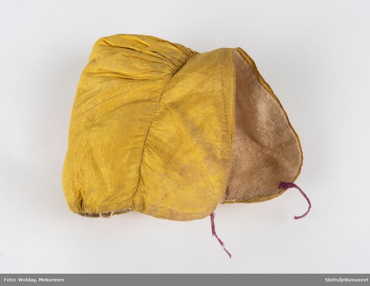Jentelue, Gul silke, foret med hvit flanell. Glatt framstykke, innsvinget ved pannen, påsatt et rett stykke som er sterkt rynket øverst. I nakken løpegang til snor