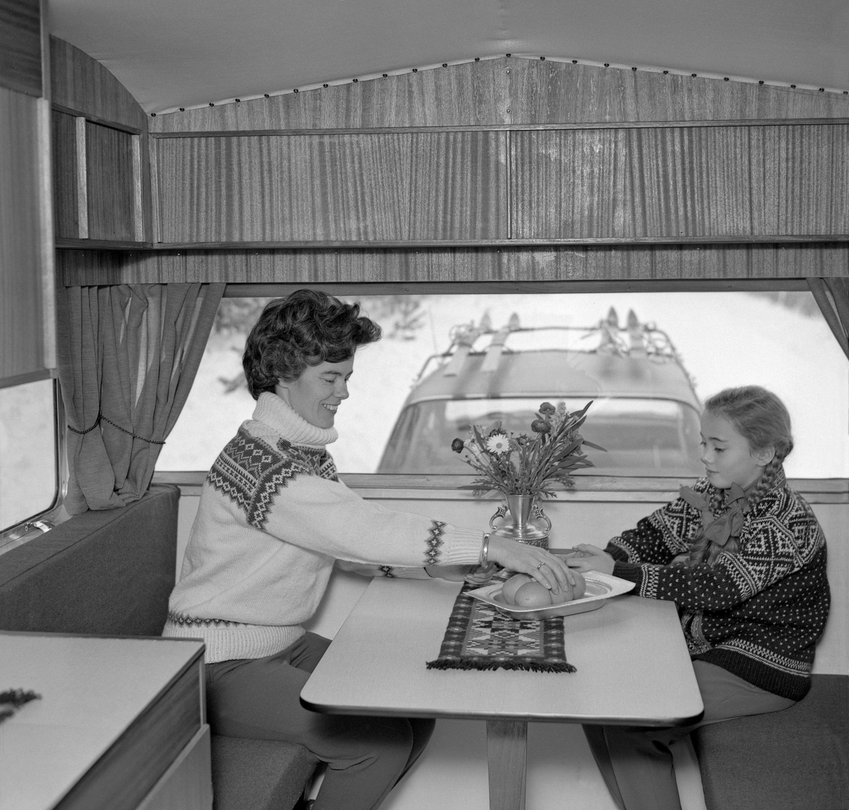 Interiør fra campingvogn, antakelig fra slutten av 1960-årene. Fotografiet er tatt mot den fremre enden av vogna, der ei ung kvinne og ei jente satt på benker hver sin side av et nedfellbart respatexbord. På bordet lå det en løper, og på den sto det et fruktfat og en vase, antakelig med plastblomster i. Da fotografiet ble tatt var de to i ferd med å forsyne seg med appelsiner. Veggene og skapdørene i vogna var lagd av finérplater med overflater av et mørkt, eksotisk treslag. Gjennom frontruta på campingvogna skimter vi taket på bilen som trakk vogna. Den hadde ski på taket. Bildet er antakelig tatt som et reklamefotografi, som skulle illustrere at campingvogna ikke bare var anvendelig sommerstid, men at den også kunne brukes i påskeferien.