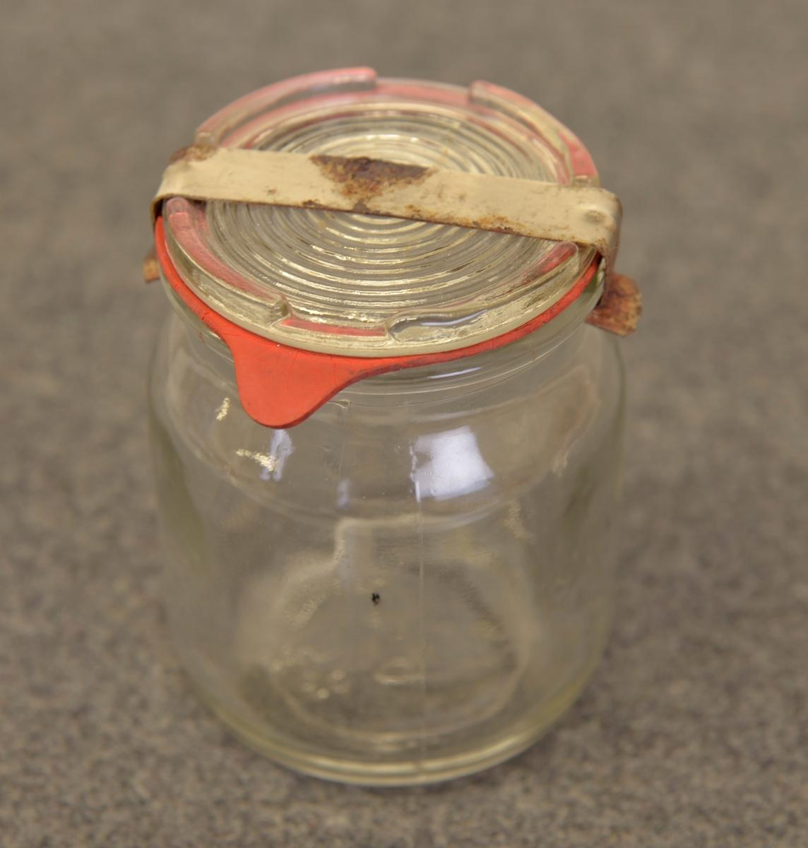 Två glasburkar med glaslock och metallbygel. Den ena har även gummiring. Locken är refflade. Märkta i botten med S och tre stjärnor, under detta siffrorna 250.  Innehåller 2,5 dl.  Från Arne Ekströms handelsmuseum.