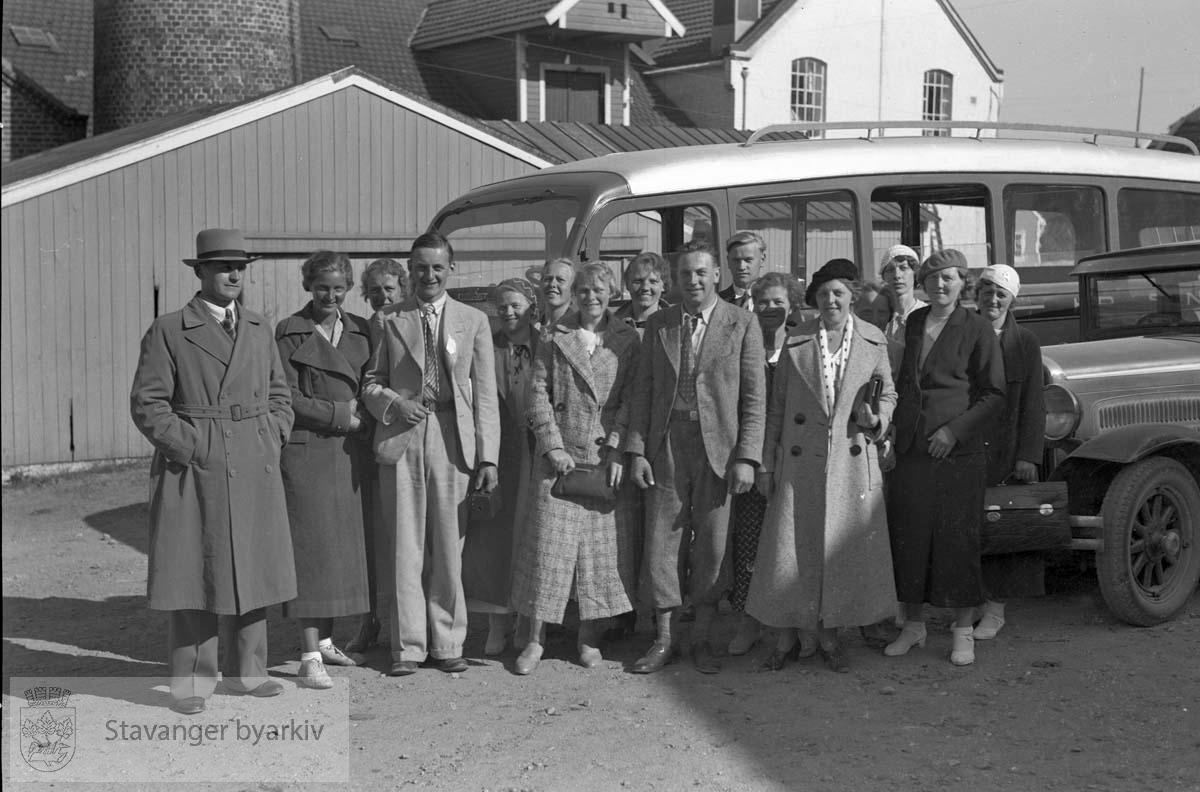 Gruppe mennesker samlet foran buss.