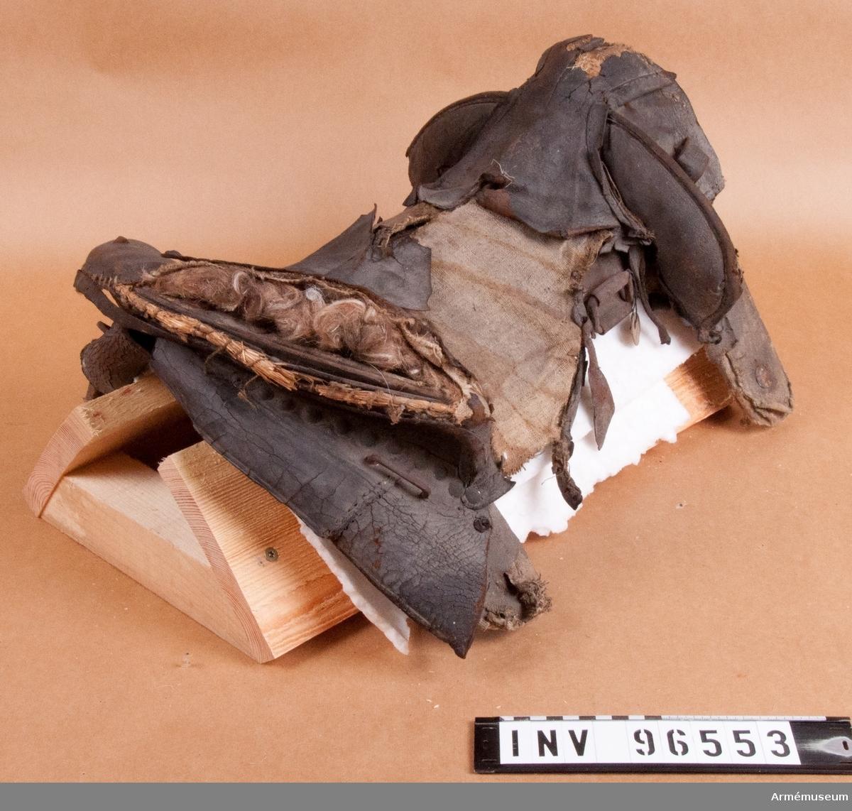 Bomsadel klädd med läder. Troligen av m/1756. Stomme av trä förstärkt med limmad väv samt järnbleck vilka följer hela böjningen av fram och bakbommarna. I de längsgående styckena är järnkrampor för stiglädren fästa. Sadelgjord är fäst i stommen för att bära upp sitsen. Sitsen är mycket trasig. Den består av ett foder av väv samt en överdel i läder. Mellan de två lagren har det har funnits stoppning och de har varit ihopfästa med en stickning som bildat ett diagonalt mönster. Sitsen går fram som en snibb över den plats där en sadelknapp ofta sitter. Bakbommen består av en vävklädd träkärna, stoppning av djurhår samt en klädsel bestående av ett lager väv och ett lager läder. Utmed bakre kanten ligger en snodd av halm som stoppning. Även bakbommen har haft stickning vilken nu försvunnit. Två krampor av järn sitter på höger och vänster sida vid bakbommen. Troligen för de packremmar som ska hålla kappsäcken på plats. Frambommarna är hela men bör vara uppbyggda på samma sätt som bakbommen. Längs framkanten på bommarna är en rad mässingstennlikor fästa såsom på bakkanten av bakbommen. Sadelkappor saknas och det tycks möjligt att dessa har skurits bort avsiktligt. Bossorna är också borta. 2015-10-19 KTS