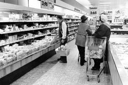 Butiksinteriör med reklamskyltar, hyllor och frysdiskar. 2 k