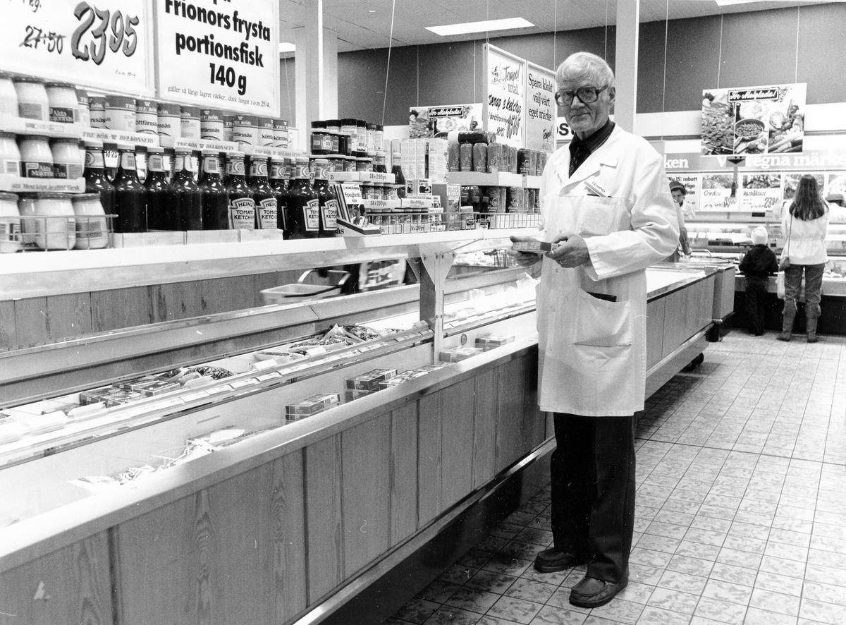 Butiksinteriör med reklamskyltar, hyllor och frysdiskar. Livsmedelschef Arne Sandberg med vit rock och glasögon står bredvid en frysdisk.