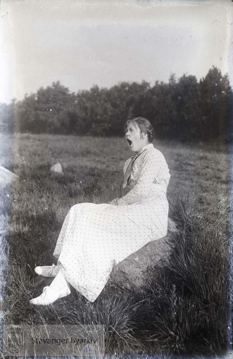 Portrett av kvinne sittende på stein
