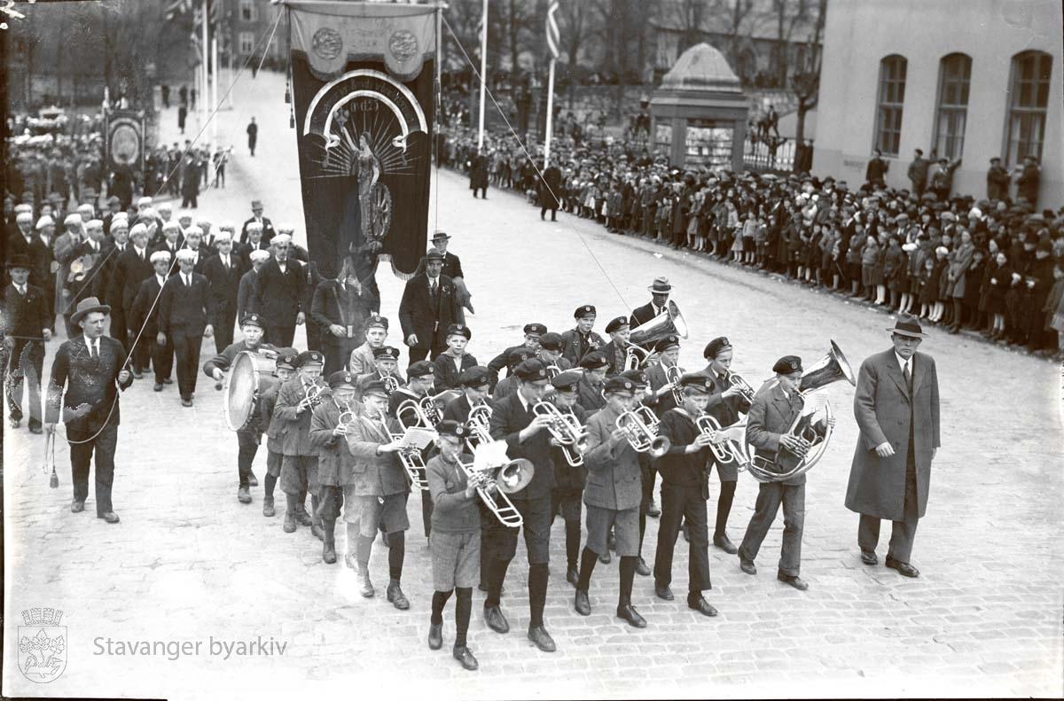 Et korps av unge gutter leder an foran fanen for Stavanger jern- & metallarbeiderforening. Tilskuere ved posthuset.