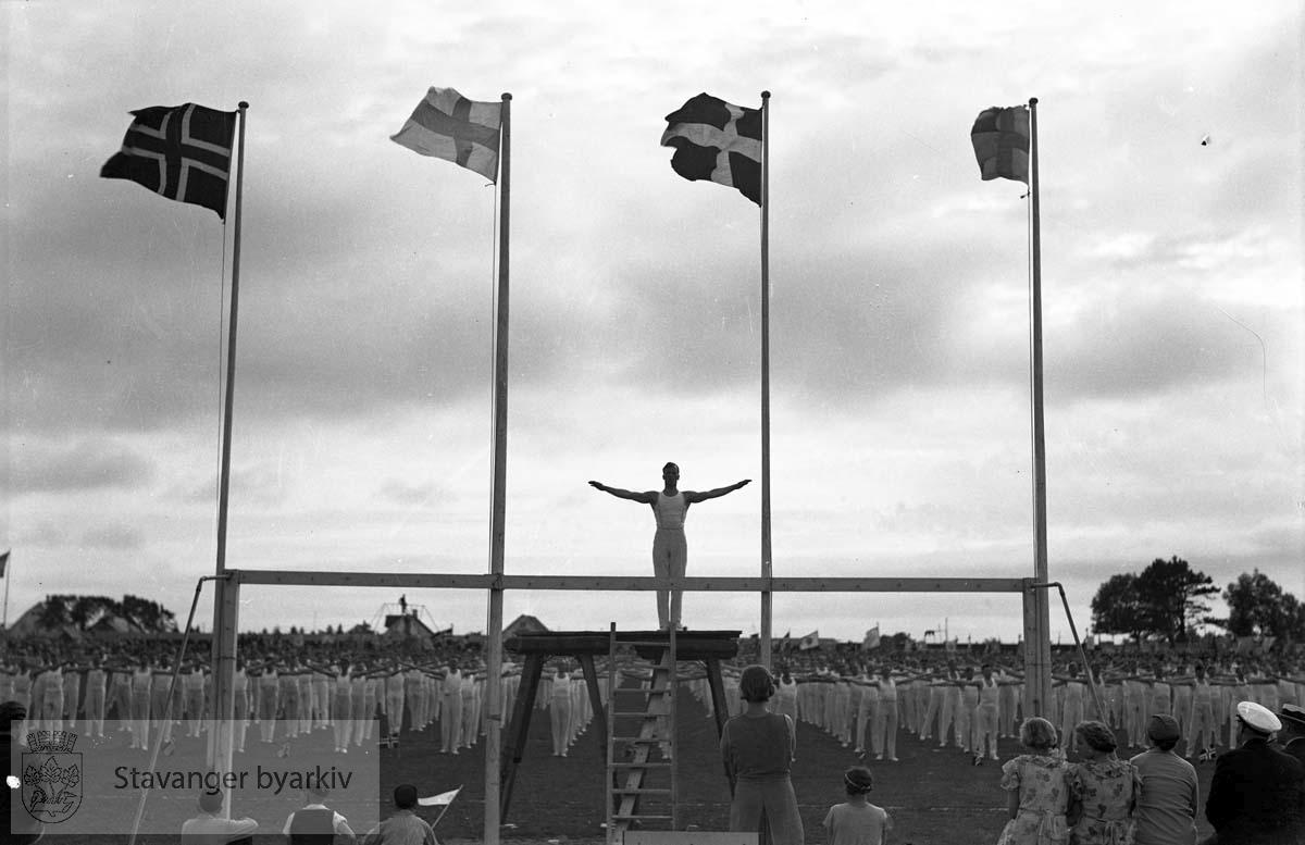 Turnstevne..Deltakere i øvelser på gressmatta.Flagg fra deltakernasjonene