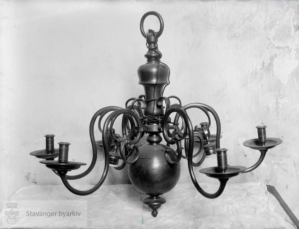 Lysekrone for stearinlys. .Ble byttet ut med Emmanuel Vigelands lysekroner i 1923.
