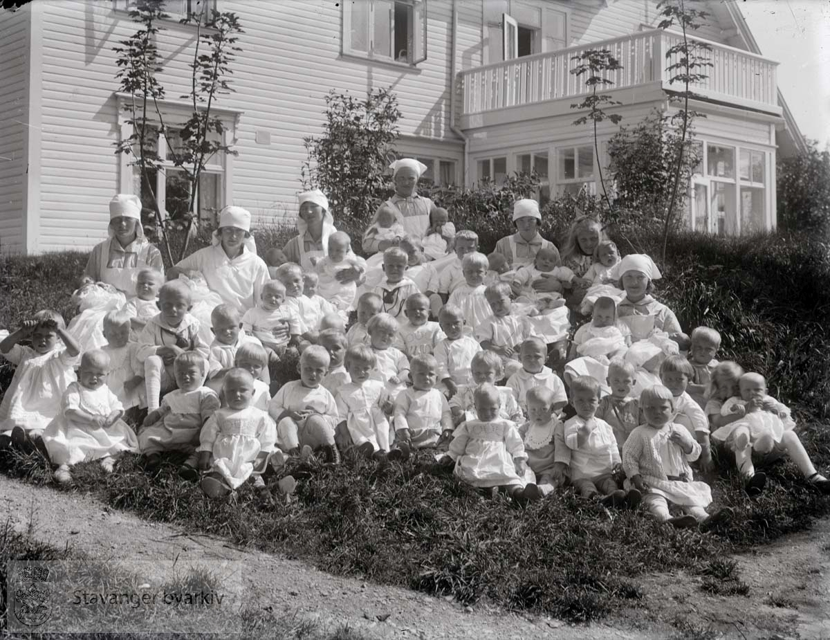 Barn med pleiersker foran hovedbygningen en sommerdag. .Strømvig spedbarnshjem