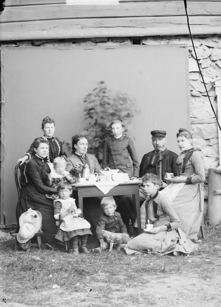Gruppe/familie med antatt 3 generasjoner rundt et kaffebord.