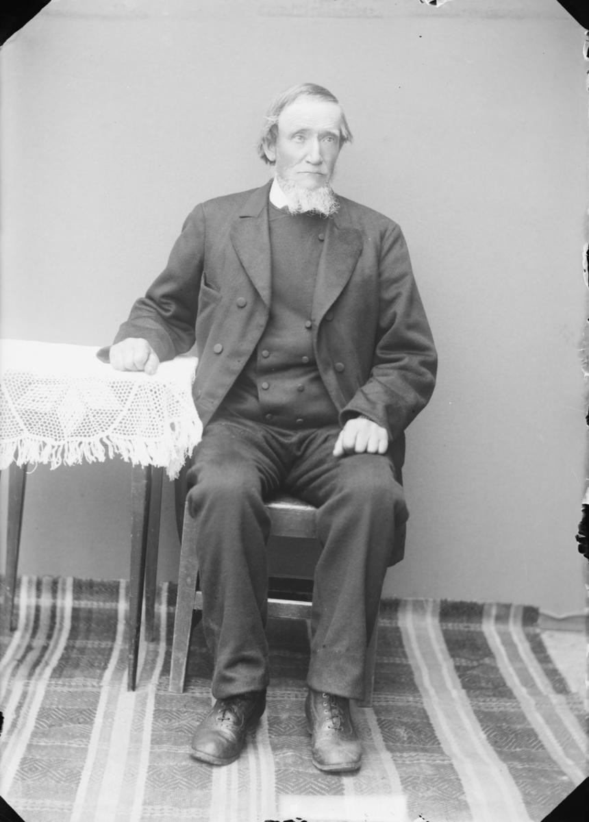Eldre mann med hvitt sjegg som sitter ved et bord