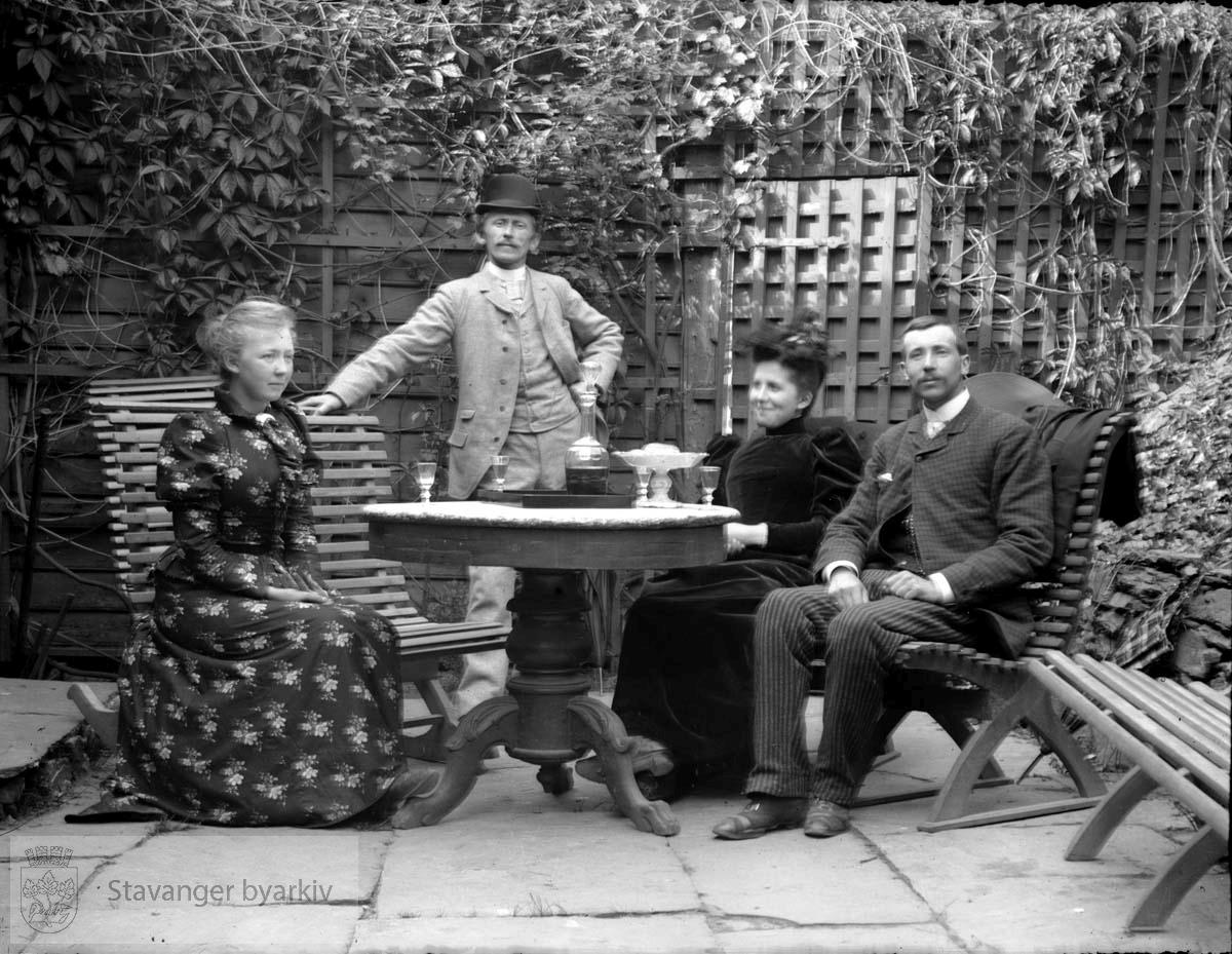 Fire personer ved hagebord i A. Abrahamsens hage, Kongsgata 32